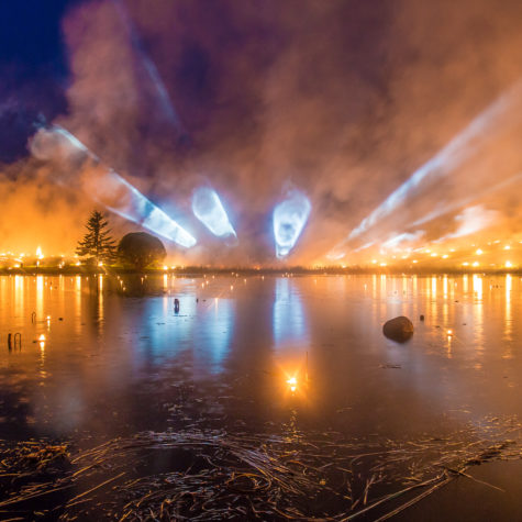 Light tubes on a horizon with a forest fire over a lake