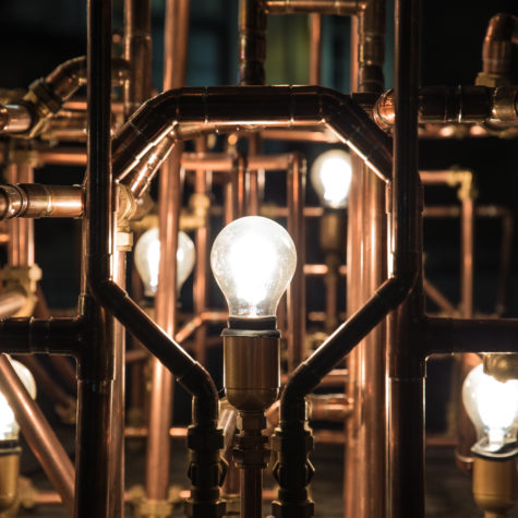 Incandescent bulbs surrounded with rusty pipes